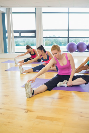 Fitness class and instructor stretching legs in bright exercise room photo