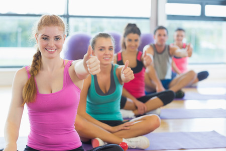 Portrait of fitness class and instructor gesturing thumbs up on yoga mats photo