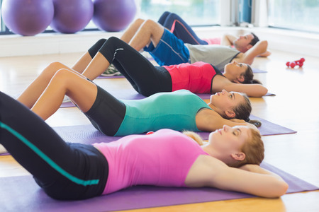 Side view of fitness class lying on exercise mats in row at fitness studio photo