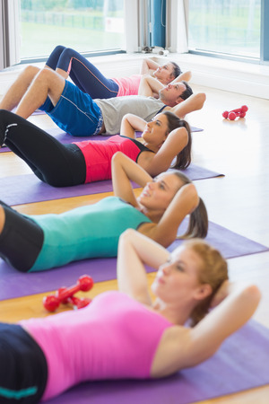 slender woman: Side view of sporty fitness class doing sit ups on exercise mats