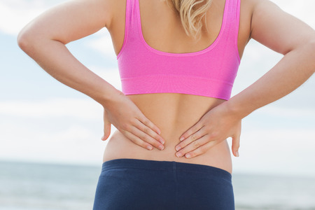 pain: Close up mid section of a healthy woman in sports bra suffering from back pain on beach