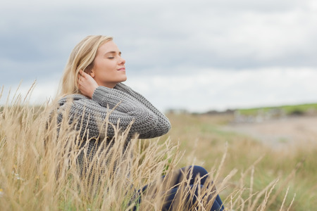 Side view of a cute thoughtful young woman sitting on grass at beach photo
