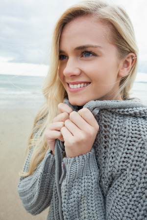 Close up of a cute smiling young woman in gray knitted jacket on the beach photo