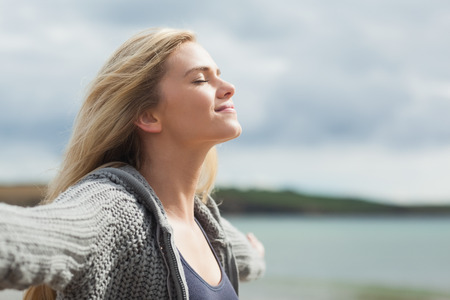 fair woman: Side view of a young woman stretching her arms on beach against the sky Stock Photo
