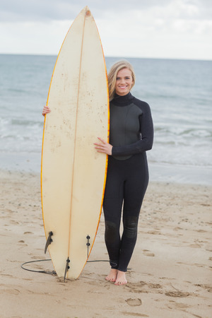 wet suit: Full length portrait of a smiling young woman in wet suit holding surfboard at beach Stock Photo