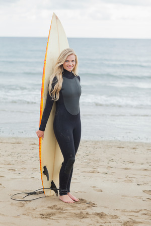 Full length portrait of a smiling young woman in wet suit holding surfboard at beach Stock Photo