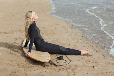 wet suit: Side view of a beautiful blond in wet suit with surfboard at the beach