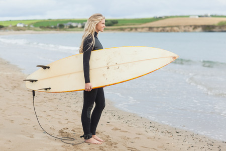 wet suit: Full length side view of a beautiful young woman in wet suit holding surfboard at the beach Stock Photo