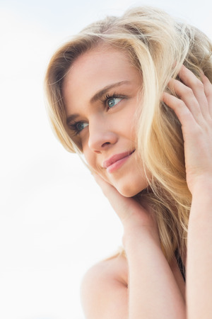 escapism: Close up of a smiling relaxed young blond looking away at the beach Stock Photo