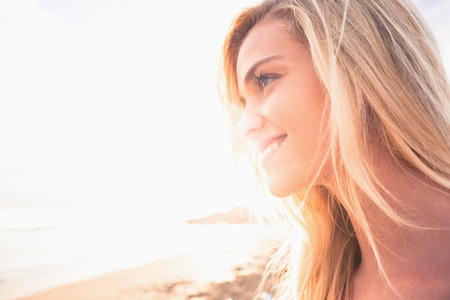 thoughtful woman: Close up of a smiling relaxed young blond looking away at the beach Stock Photo