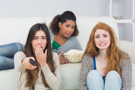 Portrait of scared young female friends with remote control and popcorn bowl on sofa at home photo