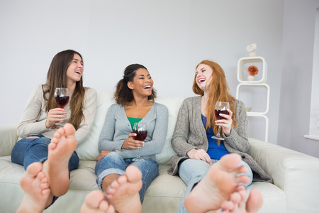 red sofa: Cheerful young female friends with wine glasses sitting on sofa at home