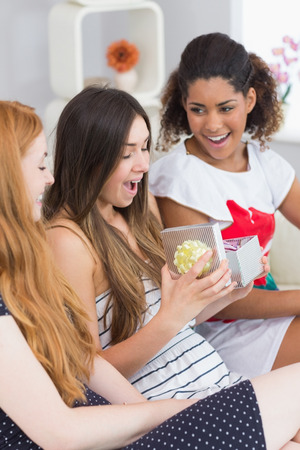 gifting: Cheerful young women surprising friend with a gift on sofa at home