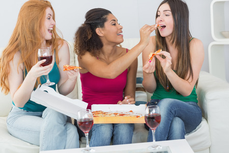 Happy young female friends eating pizza with wine on sofa at home photo