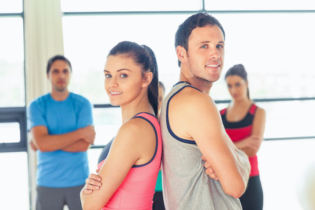 Portrait of a fit couple with friends standing in background in bright exercise room photo