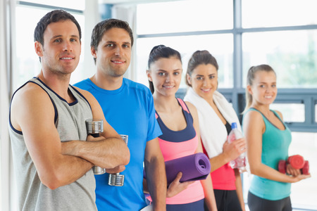 Portrait of a group of fitness class standing in row at a bright exercise room photo