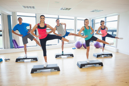 Full length portrait of instructor with fitness class performing step aerobics exercise in gym photo