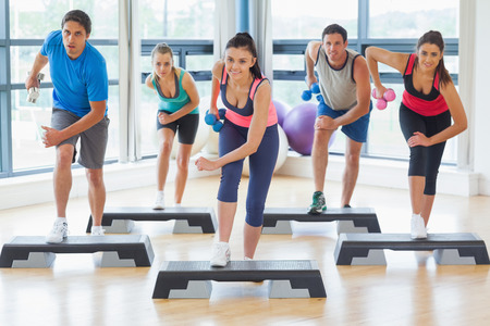 Full length of instructor with fitness class performing step aerobics exercise with dumbbells in a gym photo
