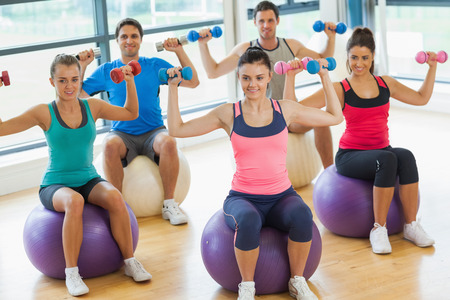 Smiling young people exercising with dumbbells on fitness balls in the bright gym photo