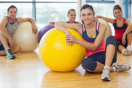 Portrait of an instructor and fitness class with exercise balls at a bright gym photo