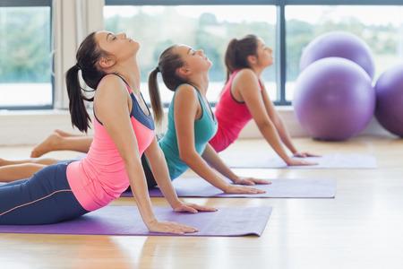 Zijaanzicht van de trainer met de klas het doen van de cobra stelt in heldere fitness-studio Stockfoto