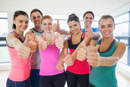 Portrait of fitness class gesturing thumbs up at a bright exercise room photo