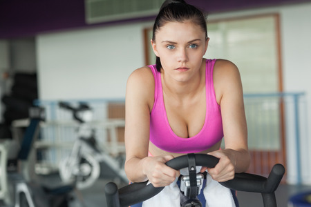Determined young woman working out at spinning class in gym photo