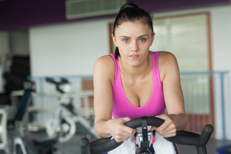 Portrait of a determined young woman working out at spinning class in gym photo