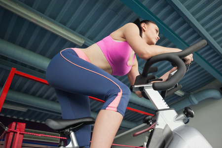 stationary bike: Low angle view of a determined young woman working out at spinning class in gym