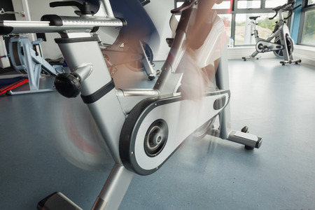 Close up low section of a determined woman working out at spinning class in gym photo