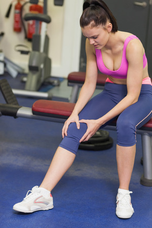 Full length of a healthy young woman with an injured knee sitting in the gym photo
