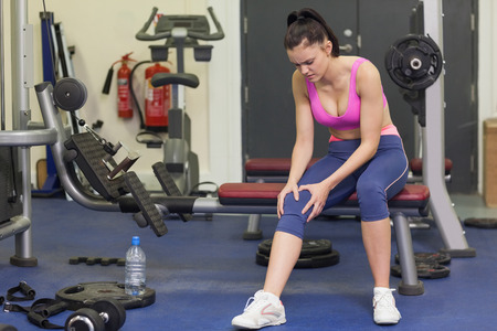 tied down: Full length of a healthy young woman with an injured knee sitting in the gym