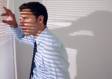Side view of a young businessman peeking through blinds in office Stock Photo