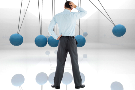 newton's cradle: Thoughtful businessman with hand on head against blue newtons cradle