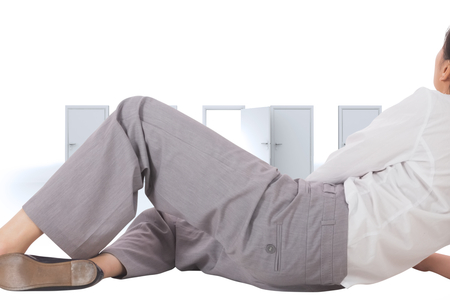Relaxed businesswoman lying against door opening revealing bright light
