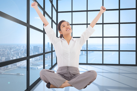 Cheering businesswoman sitting cross legged against room with large window showing city photo