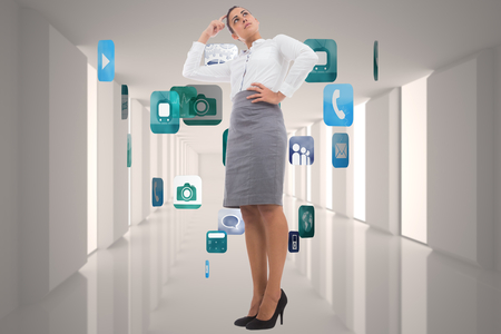 Focused businesswoman against grey room with application icons photo