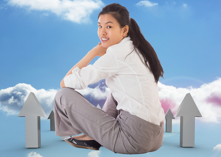 Businesswoman sitting cross legged smiling against red and grey arrows pointing up against sky photo