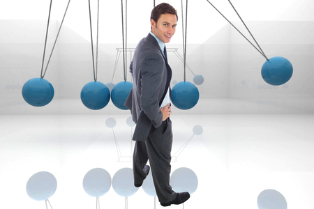 Cheerful businessman standing with hands on hips against blue newtons cradle photo