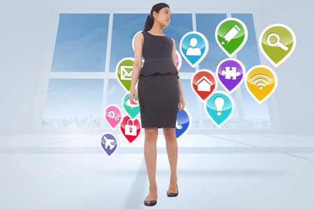 Asian businesswoman walking against app icons in white room photo