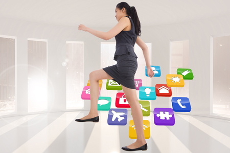 Businesswoman stepping up against application icons in white room photo