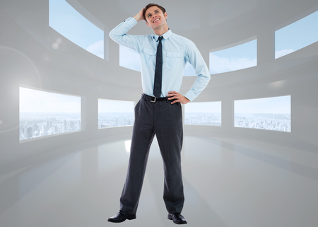 Thoughtful businessman with hand on head against bright white room with windows photo
