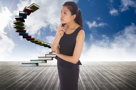 Thoughtful businesswoman against book steps against sky Stock Photo - 26777270