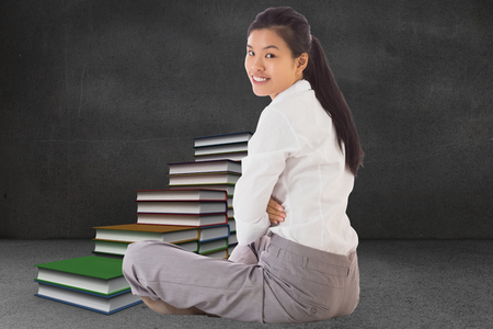 Businesswoman sitting cross legged smiling against steps made from books in grey room Stock Photo