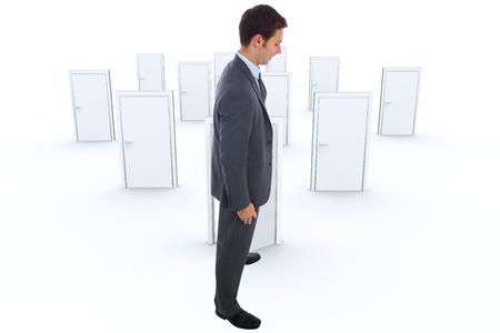 many doors: Cheerful businessman standing with hands on hips against many doors closed shut with one opening Stock Photo