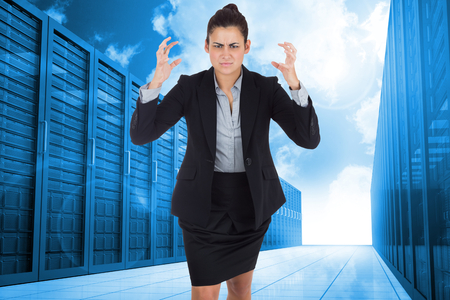 Angry businesswoman gesturing against server hallway in the blue sky photo