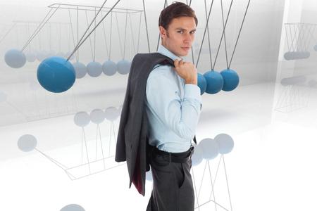 newton's cradle: Serious businessman holding his jacket against blue newtons cradle Stock Photo