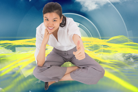 Businesswoman sitting cross legged showing thumb up against abstract yellow design on blue and white photo