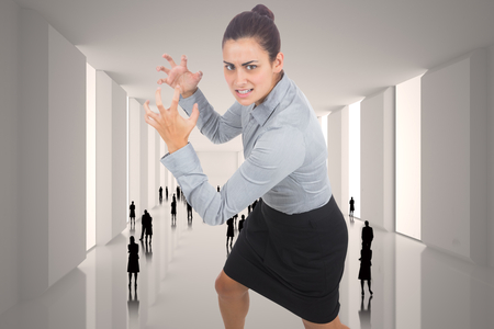 Furious businesswoman gesturing against tiny figures in huge hall photo