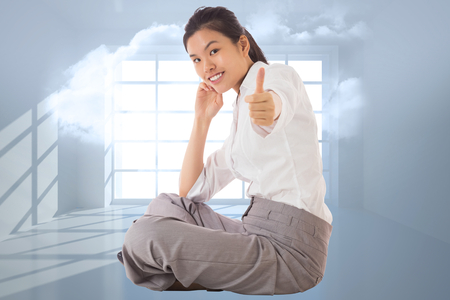 Businesswoman sitting cross legged showing thumb up against room with holographic cloud photo
